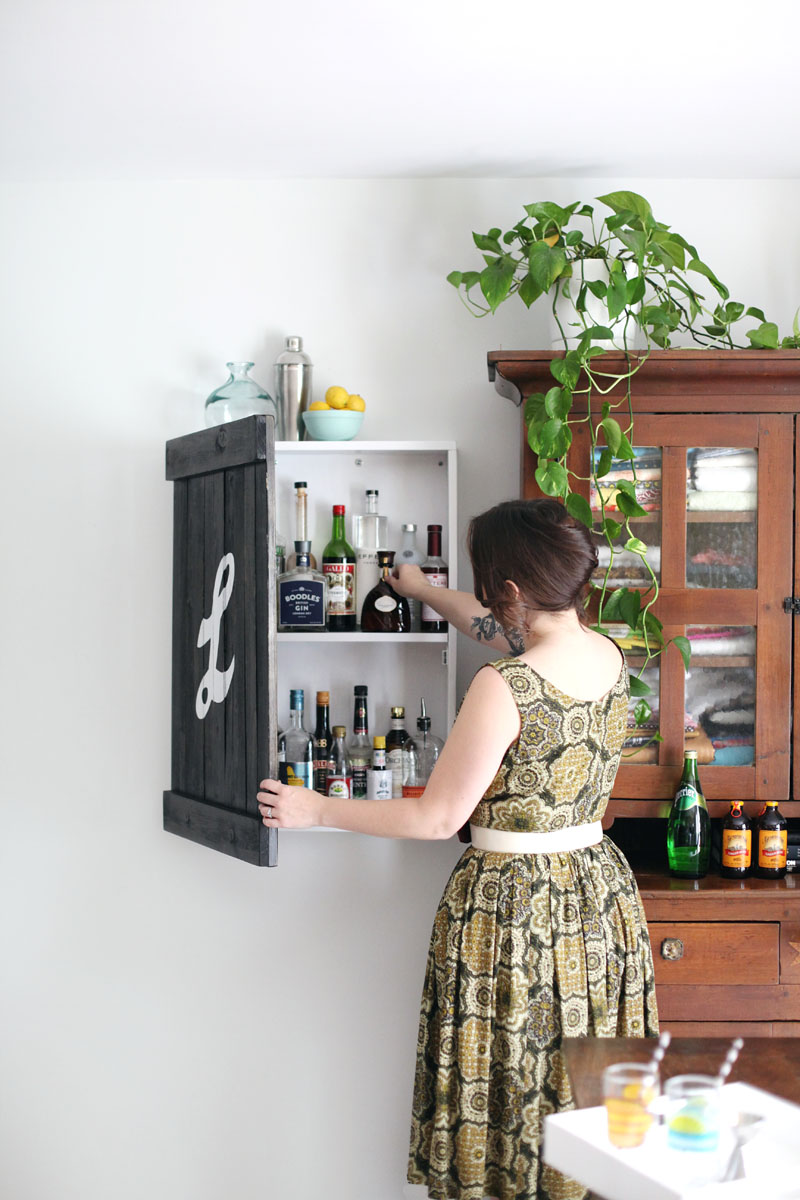 No room for a bar cart in your home? Build this wall-mounted liquor cabinet that looks like a vintage sign!